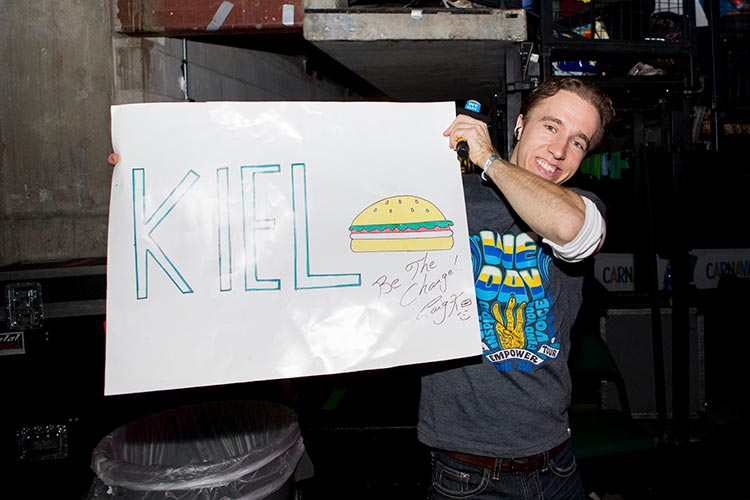 Craig Kielburger Holding a burger sign: be the change