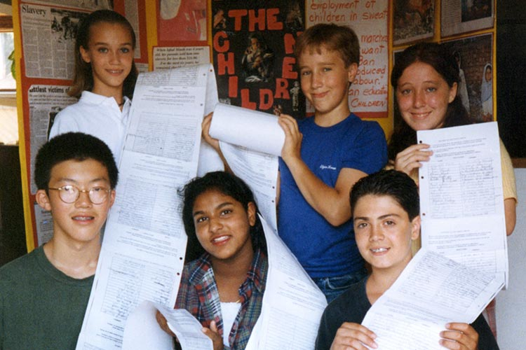 Craig Kielburger Holding the Save the children petition with other children